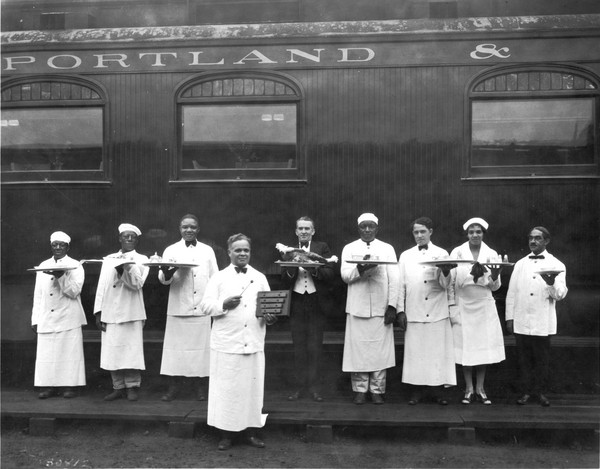 Waiters posing in front of the Northern Pacific's Spokane-Portland-Seattle run in 1915. William H. Rutherford (far right) was recruited by the Portland Hotel from Columbia, South Carolina in 1897.