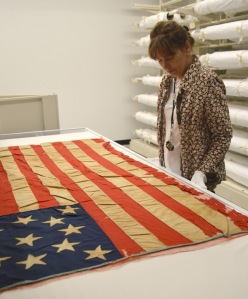 Mary Gallagher, Collections Manager at BCHS, caring for a historic flag at BCHS.